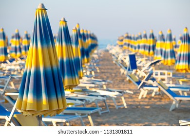 Blue and yellow umbrellas on beach on a sunny day. Famous Rimini beach background.