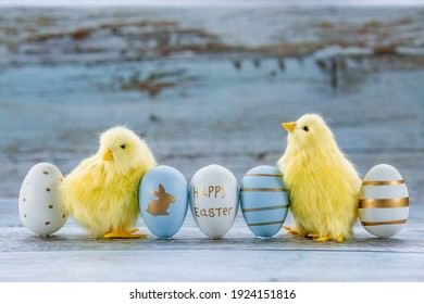 Blue, yellow, white eggs in the nest and yellow chicks on a blue wooden background. The minimal concept. An Easter card with a copy of the place for the text. - Shutterstock ID 1924151816