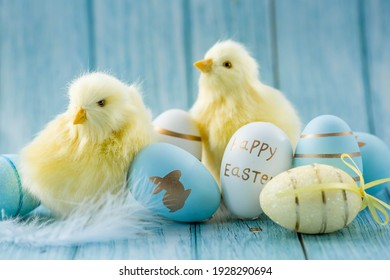 Blue, yellow, white eggs in the nest and yellow chicks on a blue wooden background. The minimal concept. An Easter card with a copy of the place for the text. - Shutterstock ID 1928290694