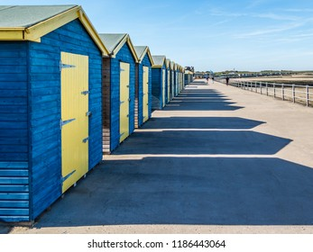 Blue and yellow wooden beach huts casting long shadows in the sunshine along the promenade at the coast of Minnis Bay, Kent, UK
