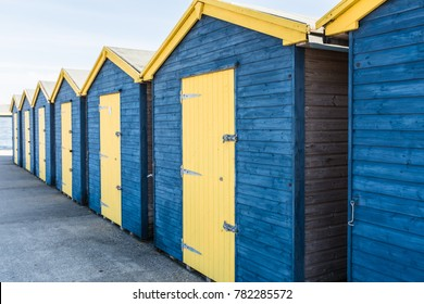 blue and yellow wooden beach huts in a row at Minnis Bay in Thanet kent, UK