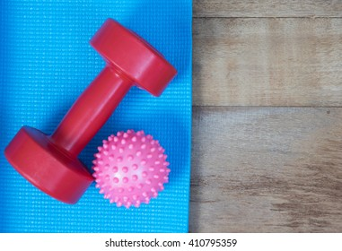Blue yoga mat and Red dumbbell on wood background