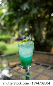 Blue Yuzu Sparkling put center on the table and put in front of nature backgrounds.(Focus Yuzu orange and Mint leaves)