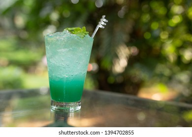 Blue Yuzu Sparkling put left on the table and put in front of nature backgrounds.(Focus tube ice)