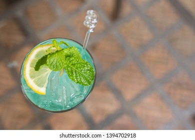 Blue Yuzu Sparkling put left on the table and shoot it bird eye view backgrounds.(Focus Yuzu orange and Mint leaves)