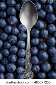 Blueberries around spoon close up photo. Natural healthy food. Still life photography