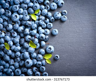 Blueberries background. Blueberry border design. Ripe and juicy fresh picked bilberries close up. Copyspace for your text