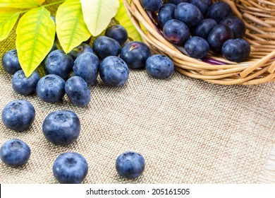 Blueberries in basket with leaves on linen cloth