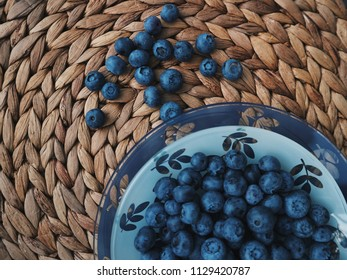 Blueberries in a beautiful bowl, on a wooden background. Fresh berries on a table. Top view.