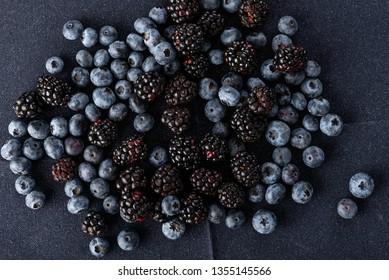Blueberries and blackberries on dark blue background.