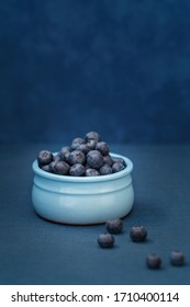 Blueberries in a blue bowl on a blue background