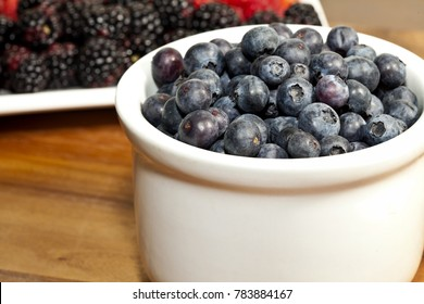 Blueberries in bowl with blackberries and raspberries in the background on wood.