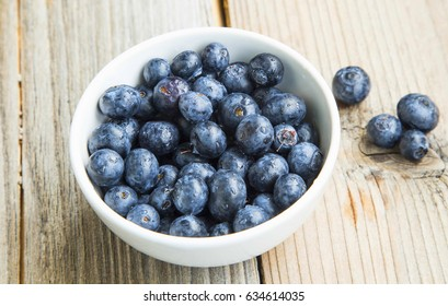 Blueberries in a bowl, healthy berry fruits in white bowl on wooden background