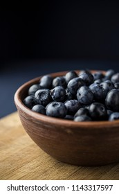 Blueberries in the bowl on a black slate