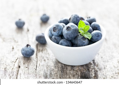 blueberries in a bowl on wood