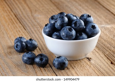 Blueberries in bowl on wooden background