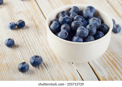 Blueberries in a bowl on  wooden table. Selective focus