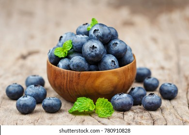 Blueberries in a bowl on wooden table, Healthy eating and nutrition concept