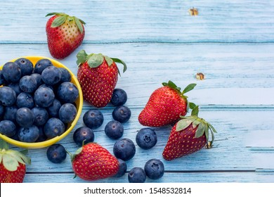 Blueberries in a bowl and some strawberries on a wooden background. Healthy lifestyle concept