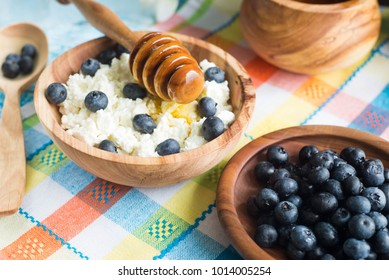 Blueberries with cottage cheese and honey in wooden utensils