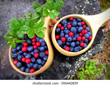 Blueberries and cranberries in wooden dishes.