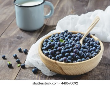 Blueberries and cup of milk on a wooden table