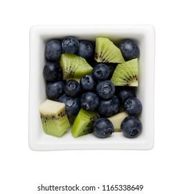 Blueberries and diced kiwifruit in a square bowl isolated on white background