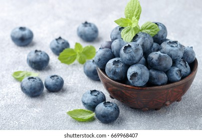 Blueberries. Fresh organic berries in clay bowl and fresh mint leaves on a stone or concrete background. Natural antioxidant superfood. healthy food concept
