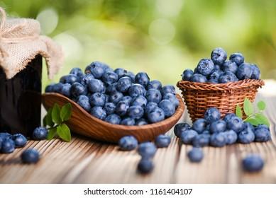 Blueberries fruits in wicker basket on old wooden table. Blueberry jam or marmelade in glass bottle.