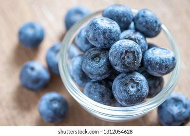 Blueberries in a glass bowl on wooden table and texture, fresh fruit with water droplet