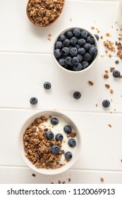 Blueberries, granola and yoghurt on wooden background