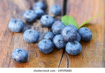 Blueberries with green leaves on a old wooden table