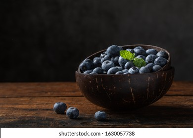 Blueberries or huckleberries and mint leaf in a coconut bowl. The bowl is on a rustic wooden table with a gray background. There are some blueberries outside the bowl.