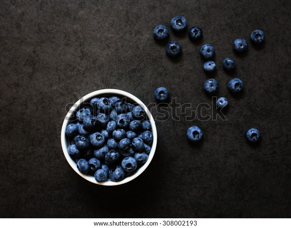 Blueberries into a white bowl and a handful of berries on a grey background
