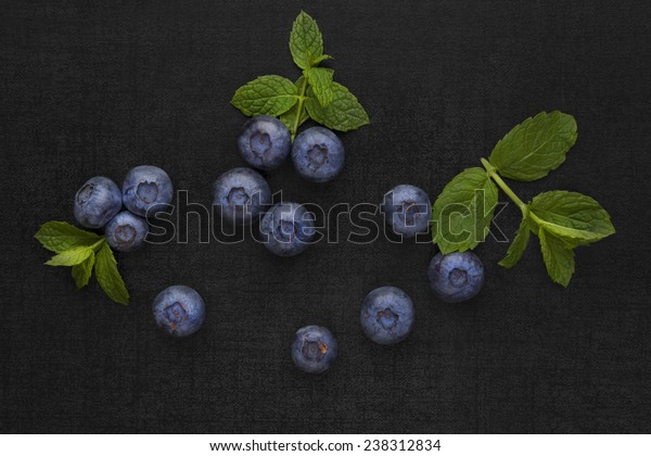 Blueberries isolated on black background with green mint leaves. Healthy fresh seasonal fruit eating.