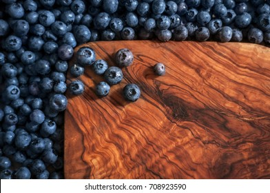 Blueberries isolated on wooden background. Blueberry border design. Ripe and juicy fresh picked bilberries close up. Copy space. Top view or flat lay