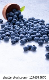 Blueberries and leaves scattered on light flat surface background - Image