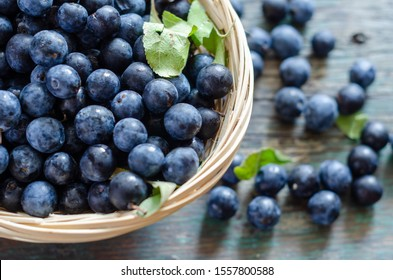 Blueberries with blueberries leaves in the wooden bowl on the table.