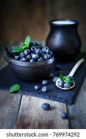 Blueberries with mint on a stone tray with milk