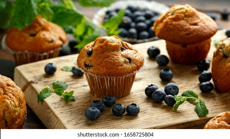 Blueberries muffins, cupcake with mint and berry on wooden board.