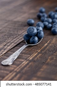 Blueberries on old spoon on grunge wooden board. Natural healthy food. Still life photography