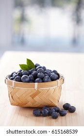 Blueberries on terrace table over nature background. Fresh blueberries in wooden bowl. health food concept
