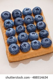 Blueberries on top of sweet waffle on plate closeup. Still life