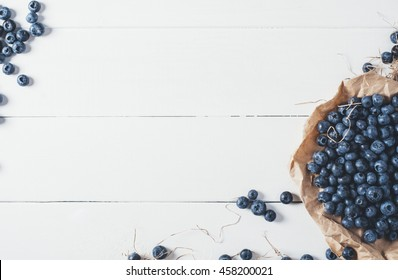 Blueberries on vintage wooden white background top view, healthy food on dark table mockup, berry for smoothie on vintage rustic country board, fresh bilberry mock up closeup, copy space for text