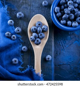 Blueberries on wooden spoon. Blue bright background