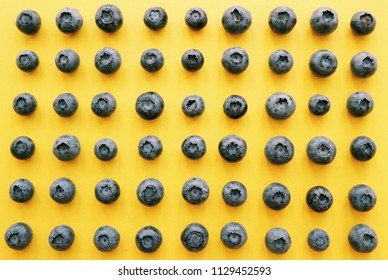 Blueberries on a yellow background. Blueberry pattern. Fresh summer pattern. Geometric pattern.