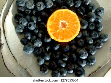 Blueberries and orange on rustic plates