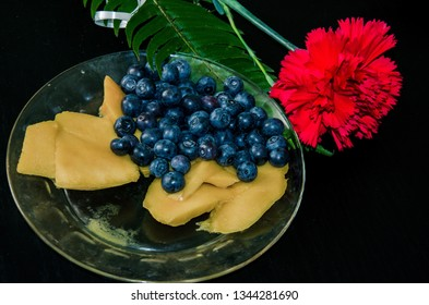 Blueberries, pieces of mango in white glass plate with red carnation on black background