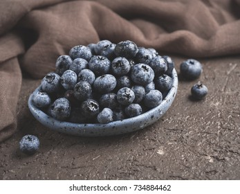 Blueberries in plate on brown concrete background. Fresh picked bilberries close up. Copyspace. Close up
