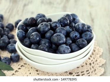 Blueberries in plates on napkin on wooden background